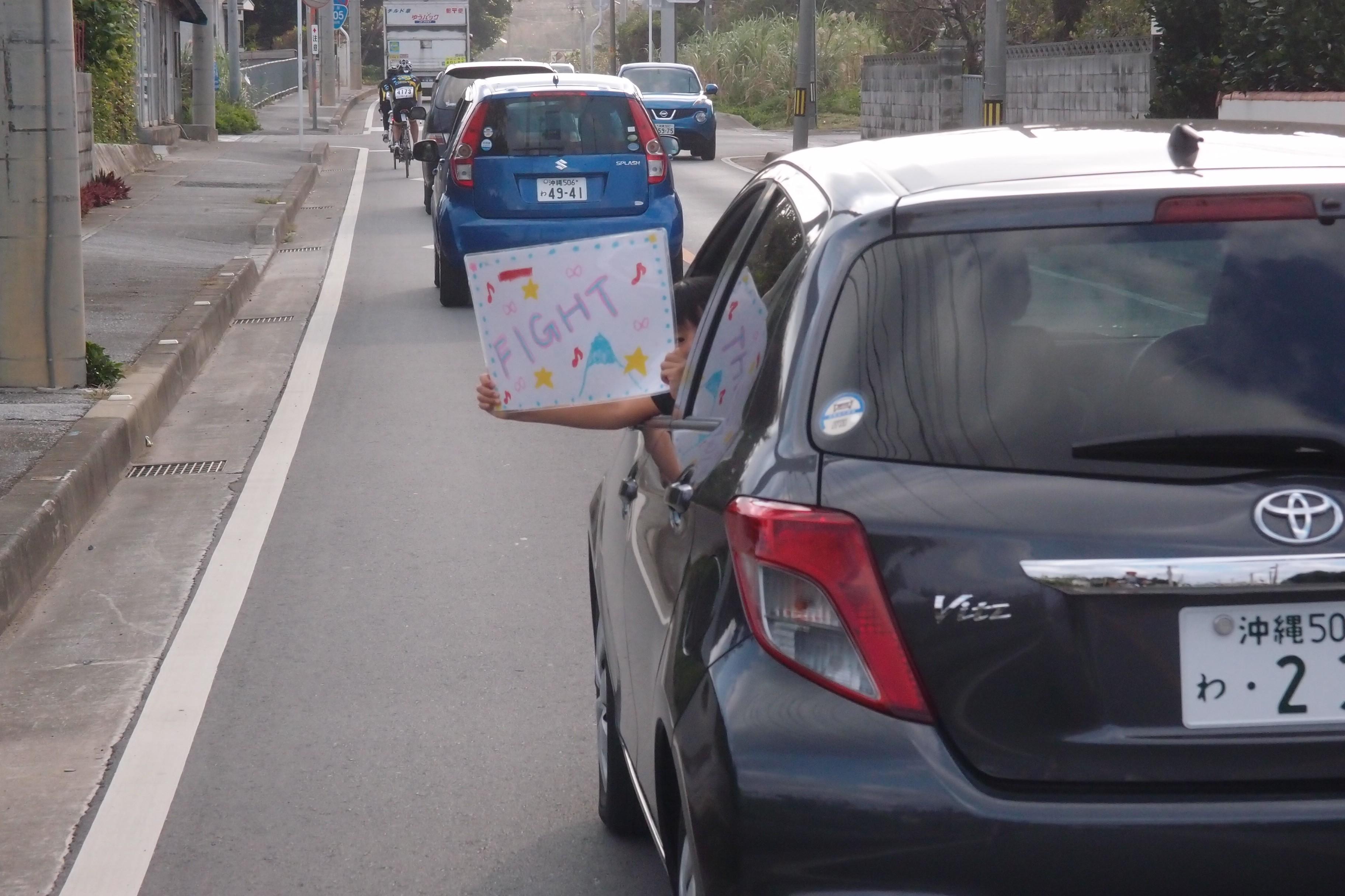 小朋友從車窗內展示為車友加油的Fight(加油)字樣。